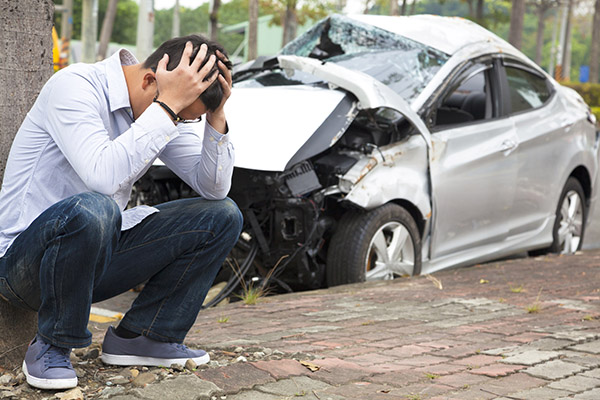 Image of young man crouching down with his hands on his heads with a crashed car behind him