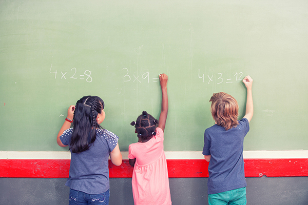 Three young children solving multiplication problems on a chalkboard