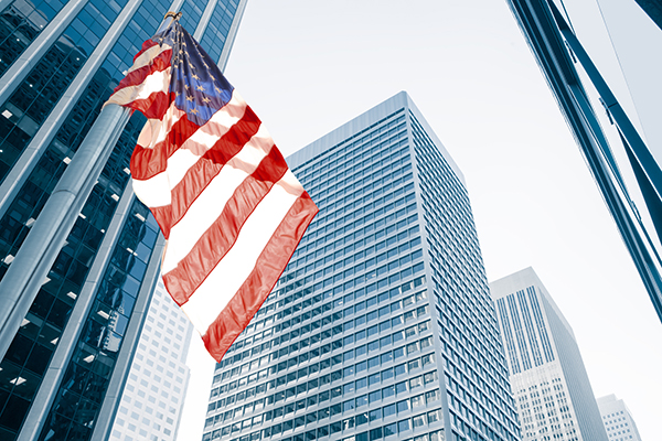 Image of American flag flying in a cityscape with skyscrapers
