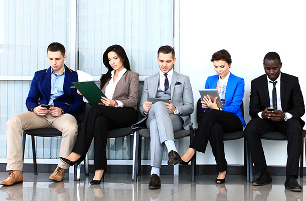 Image of white and black men and women in business attire sitting on chairs using phones and tablets