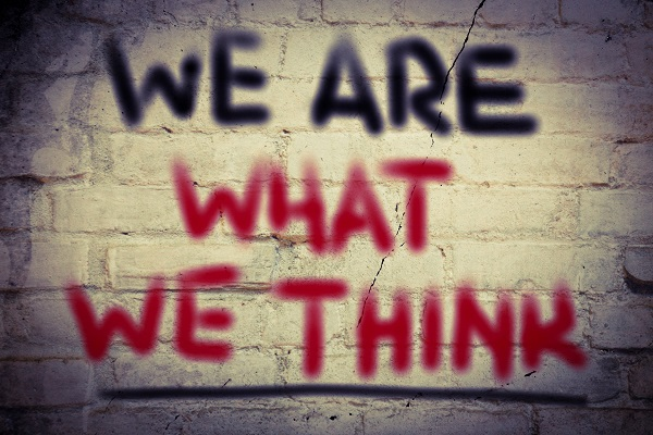 """We Are What We Think"" written in graffiti on a brick background"