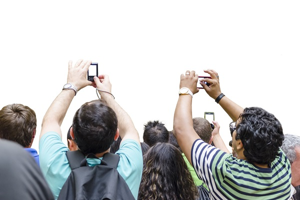 Image of a crowd of people stretching their arms in the air to take photos with their phones and cameras