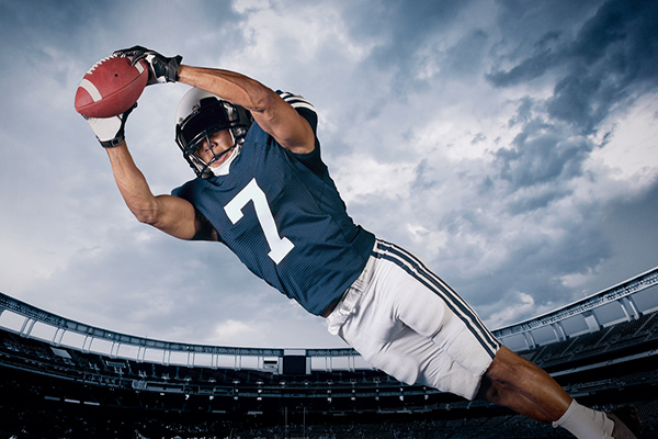 Image of American football player outstretched in the air catching the football