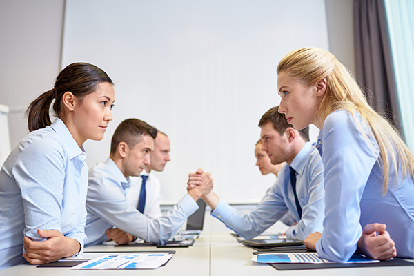 Image of opposing pairs of businessmen and businesswomen staring each other down, engaging in an arm wrestle