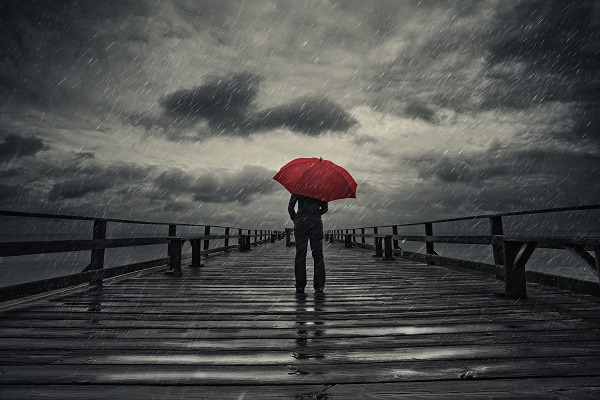 Image of someone walking down a pier in the rain holding an umbrella