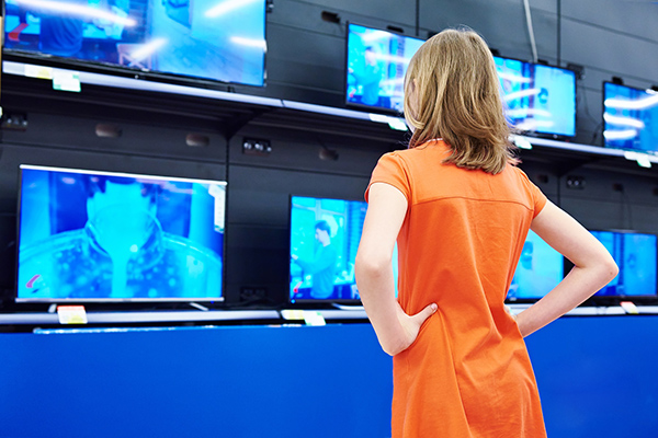 Image of young woman looking at TV screens all playing the same video
