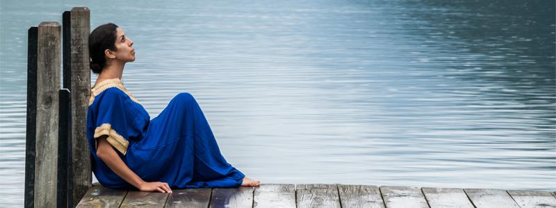 Woman sitting on a dock near a lake