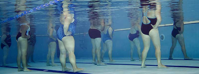 underwater view of ladies aerobics class in a pool, with various body sizes and ages