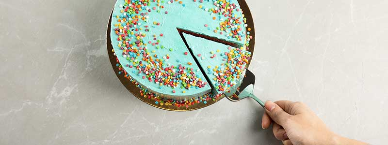 Person taking slice of fresh delicious colorful cake at table, top view