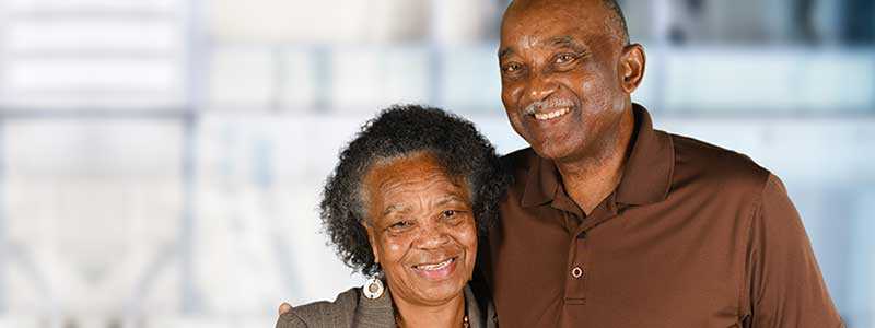 Smiling elderly couple stand close to each other