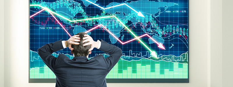 Businessman grabs head looking at business charts