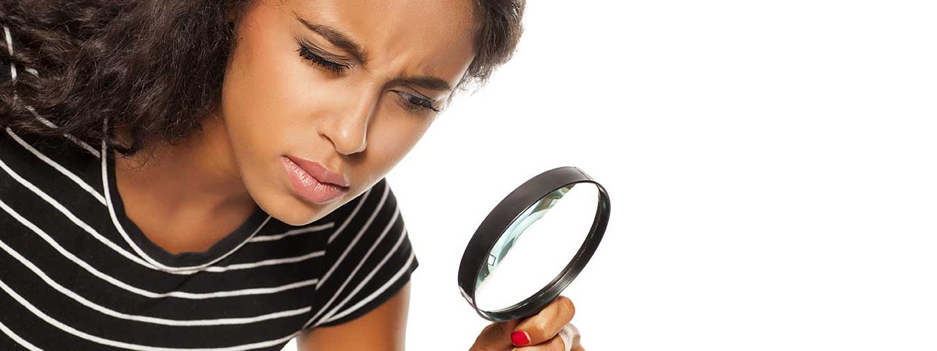 woman looking trough a magnifying glass