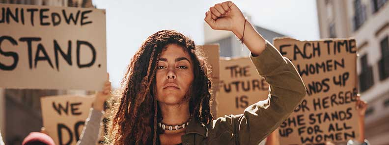 a Woman stand in a crowd with fist raised, looking powerful and strong