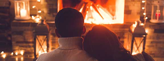 a couple dressed warmly in front of a fire in a fireplace snuggle close together