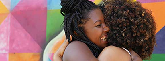 Two African-American women hug each other happily