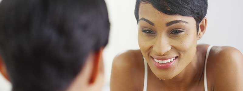 woman looking at her face in mirror, smiling