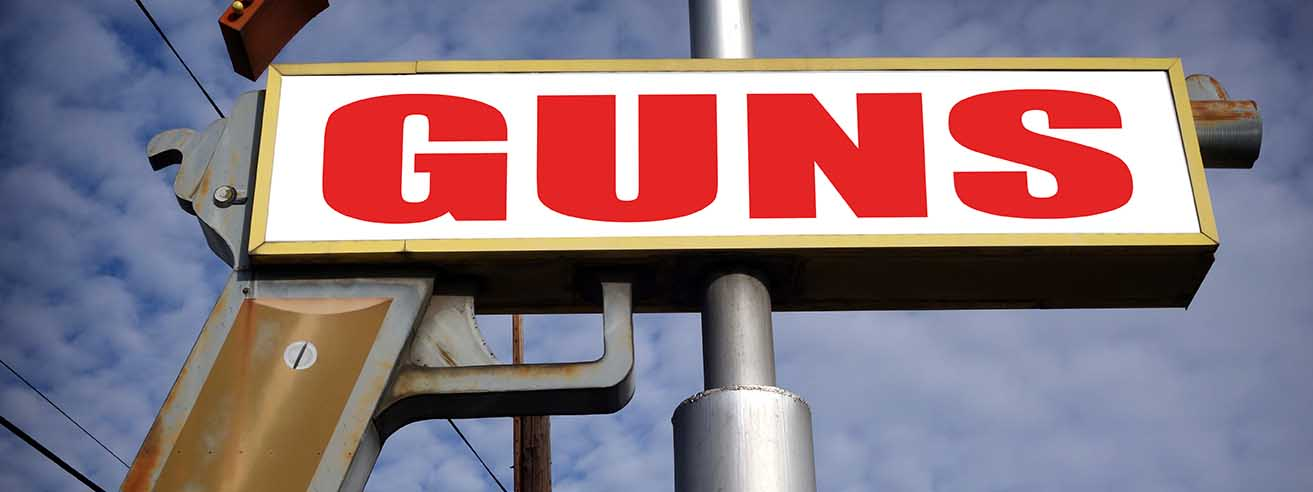 sign up high shaped like a gun with the word guns on it