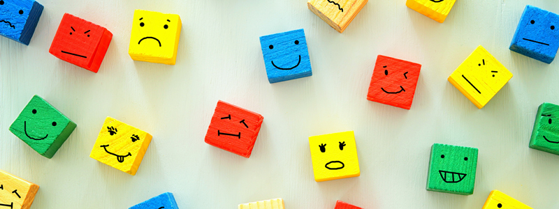 Different emotions drawn on colorful wooden blocks