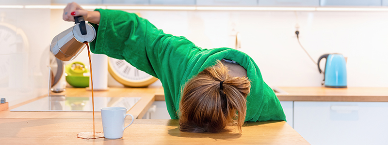 Tired woman sleeping on the table in the kitchen at breakfast