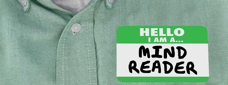 a green shirt has a hello my name is mind reader sticker on it