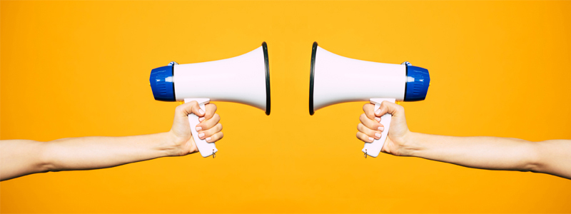 two people pointing megaphones at each other