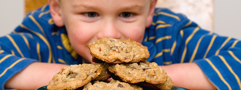 Young boy looking at plate of cookies