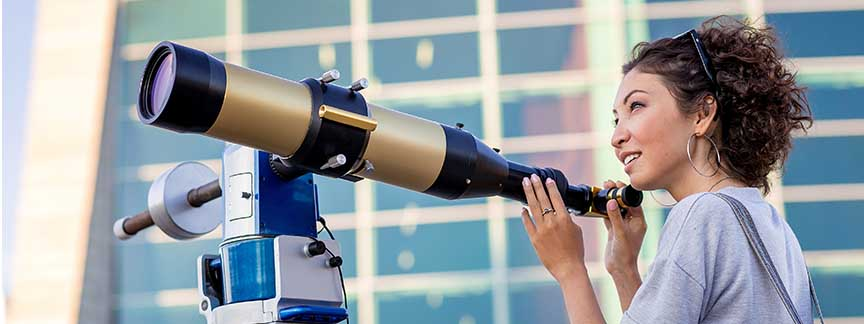 A woman looks across a telescope in front of a glass building