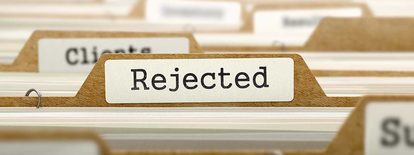 """A closeup of manila file folders. The most prominent one says """"rejection"""""""