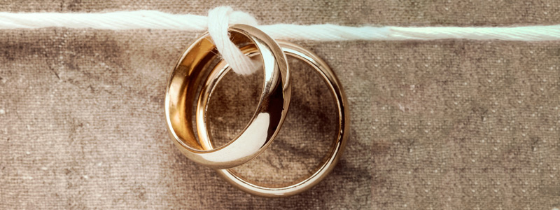 Image of two wedding bands tied together on a horizontal line of string