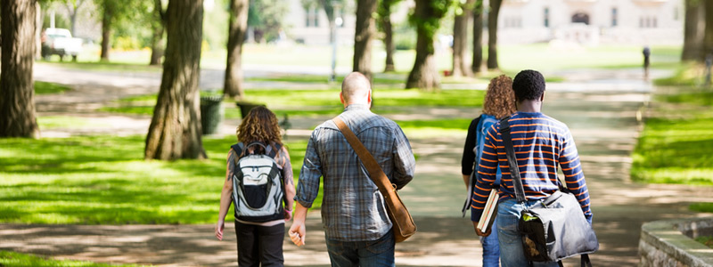 Image of mulitracial group of college students walking through a lush green college campus