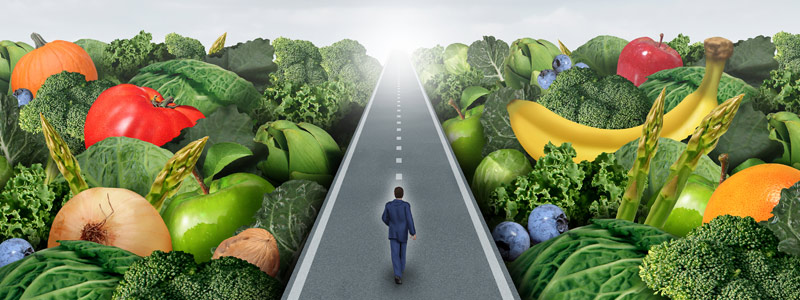 Illustration of man walking down road with fruits and vegetables creating the landscape