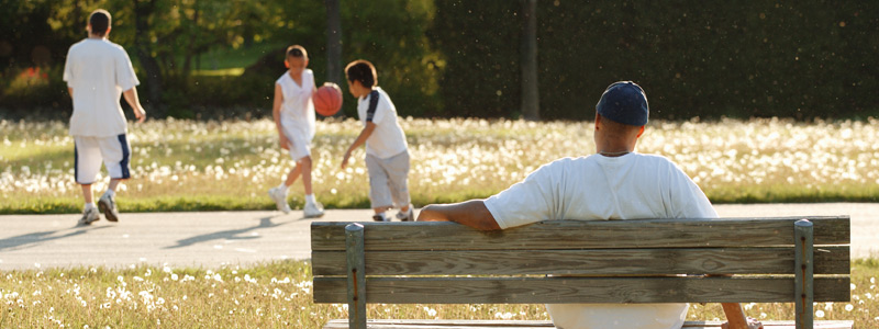 Image of man sitting on a park bench with boys play basketball