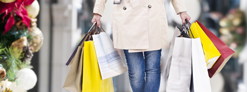 Image of woman walking with several shopping bags in each hand