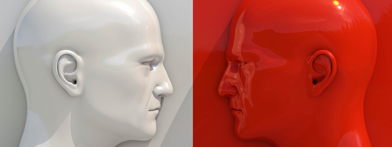 Image of two opposing face statues, the left is white the right is red