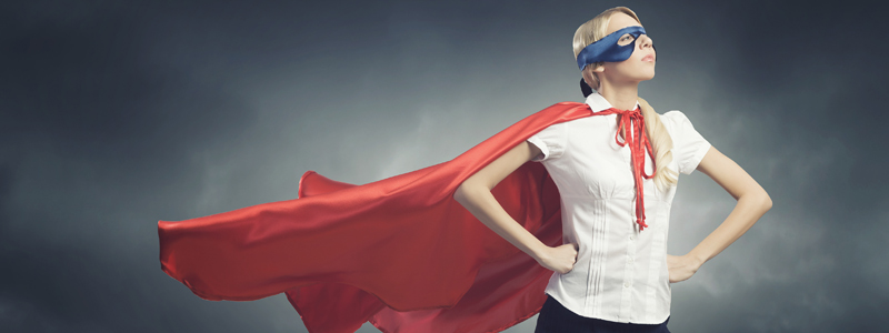 Image of empowered woman with a cape and mask on looking off into the distance with her hands on her hips.