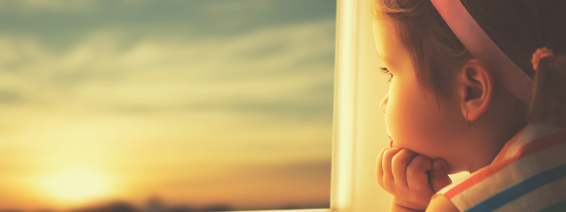 Image of sad young girl looking out the window at a setting sun
