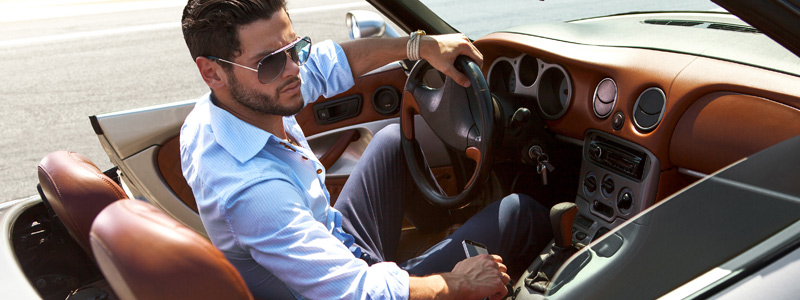 Image of well-dressed man sitting in a luxury automobile