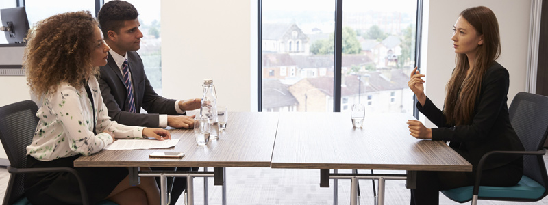 Image of a business man and business woman interviewing a woman at a table