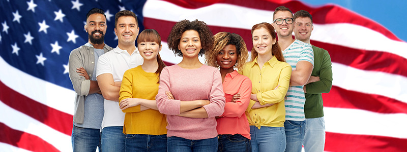 Image of men and women standing in front of an American flag
