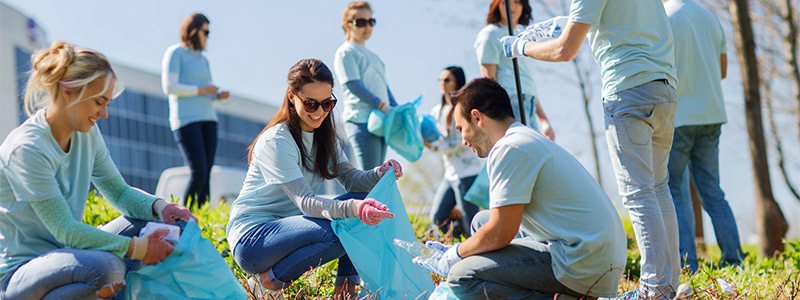 Image of young adults picking up trash and recycling