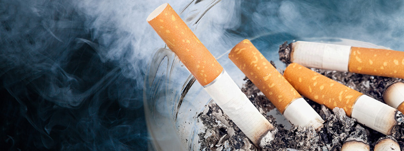 Image of smoldering, smoky cigarette butts in an ashtray