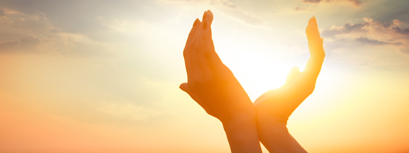 Image of hands raised to the sky in front of a sunset