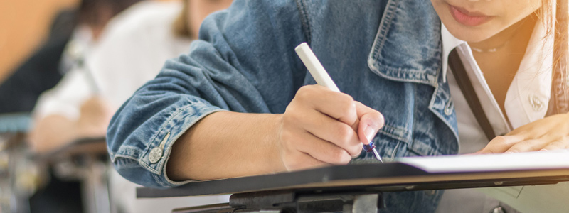 Image of young female student writing on paper at a school desk