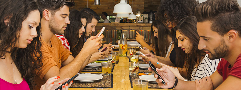 Image of young men and women sitting around a table on their smartphones