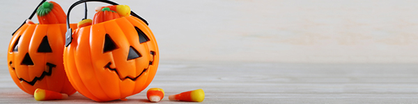 Image of two Halloween jack-o-lantern candy buckets filled with candy corn