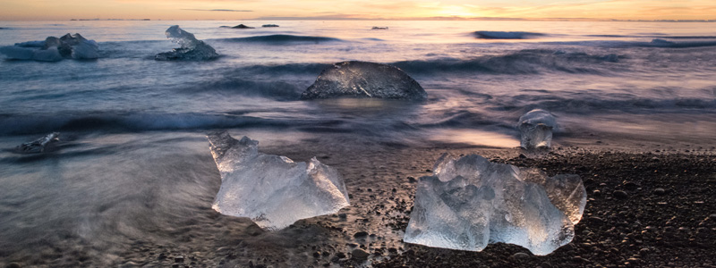 Image of blocks of ice resting on a calm beach as the sun sets