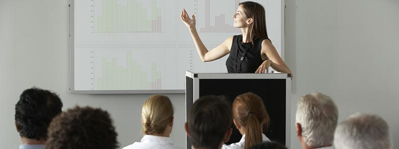 Woman stands at podium, presenting research to an small audience at a conference