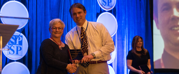 Andrew Christopher accepts Undergraduate Teaching and Mentoring Award